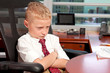 Cute young boy in a business office with mad expression