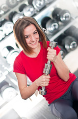 Beautiful girl with dumbbells in sport club
