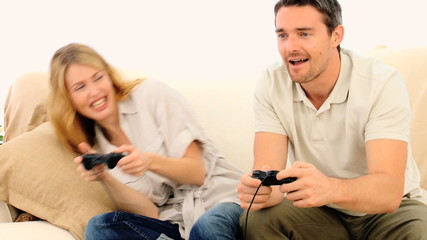 Cute couple playing a video game with with two joysticks