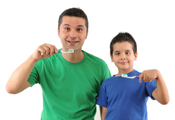Cute boy and his father brushing teeth isolated on white.