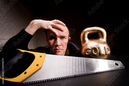 Man with saw and heavy weight of gold