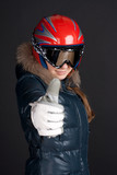 A girl in ski clothing raises a big thumbs up