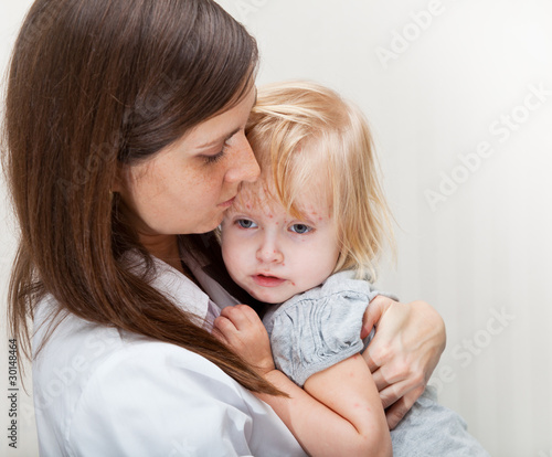 a mother is holding a sick girl.