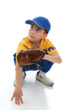 Little boy in baseball T-ball gear crouching with mitt