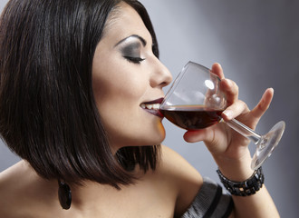 Studio portrait of a beautiful brunette drinking wine.