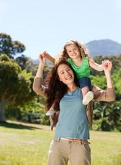 Woman giving daughter a piggyback