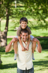Handsome man giving son a piggyback