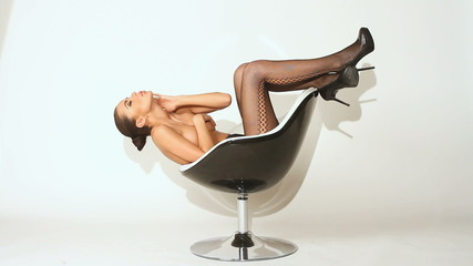 Sexy young woman posing on chair, wearing stockings