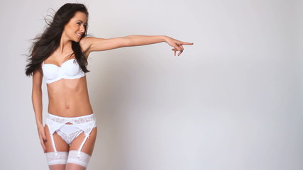 Cute female in white lingerie pointing at copyspace
