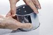 Hands installing metal pot light fixture