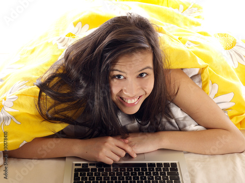 smiling girl lying in bed with a computer notebook