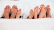Feet of a family in a bed
