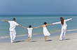 Mother, Father and Children Family Holding Hands At Beach