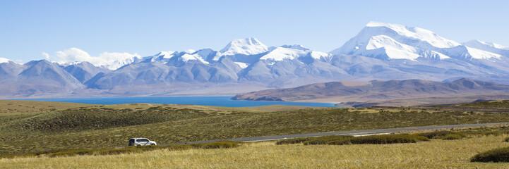 tibet: SUV passing by mount naimonanyi
