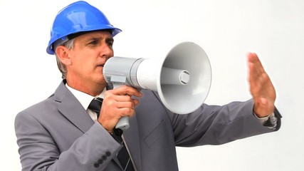 Businessman with a safety helmet and a megaphone
