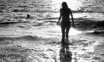 Young woman silhouetted and reflected in the sea