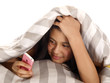 girl hiding under bed sheets with mobile phone