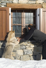 Man and dog looking at window