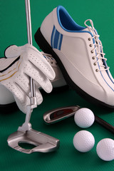 Golf shoes with glove, club and balls on green background