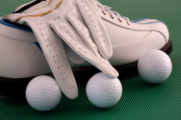 Golf shoes with glove and balls on green background