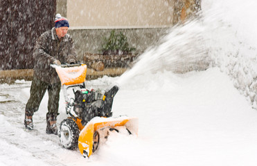 Man Using Snowblower in a snow storm