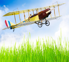 Flying biplane over a airfield.