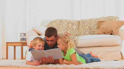 Attentive father reading a children book for his children