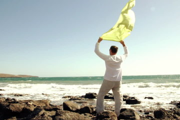 Man with waving sarong standing on the seashore, slow motion