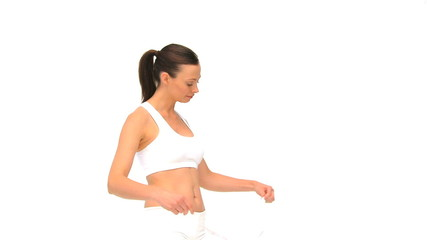 Woman measuring her waist against a white background