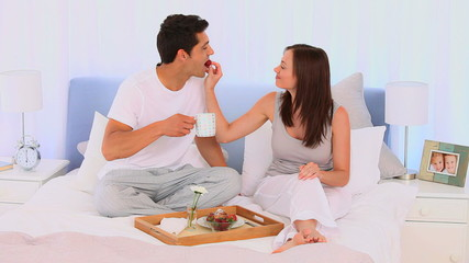 Couple having breakfast on their bed