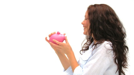 Woman putting her money in her piggy bank