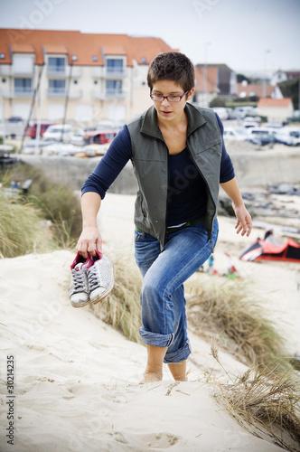 Young woman climbing a sand dune
