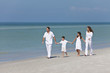 Mother, Father & Children Family Walking Holding Hands On Beach