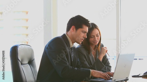 Businessman and woman working on a laptop