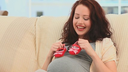 Pregnant woman holding little red shoes