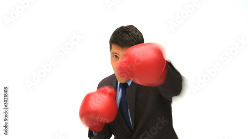 Man dressing in a business suit with boxing gloves