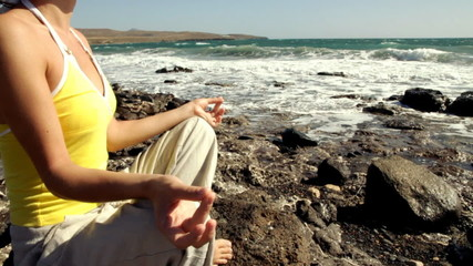 Woman meditating by the sea, slow motion, shot at 60fps