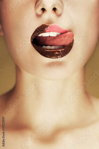 Close-up shot of beautiful woman lips with chocolate
