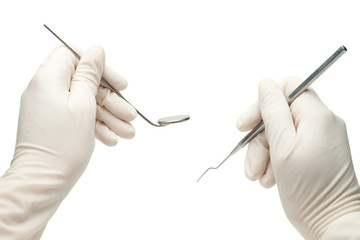 hands of dentist holding his tools during patient examination is
