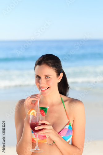 Beautiful woman drinking cocktail on the beach