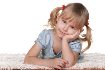 Thoughtful girl lying on the thick carpet