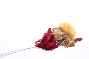 Piece of a pork steak, a dumpling and beet salad on a fork