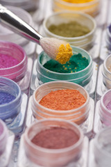 cosmetic brush pigment above containers of pigments