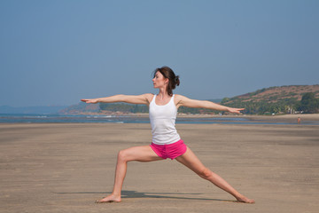 Young woman doing yoga on the beach