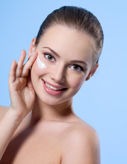 Smiling teen girl with cream on face