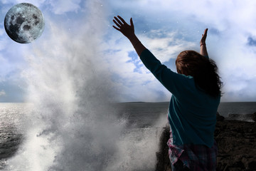 lone woman with raised hands facing a wave and full moon on clif