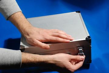 hands unlocking suitcase