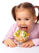 Little girl licks fruit salad