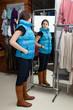 Девушка примеряет новую вещь в магазине одежды.