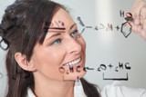female writes out a chemistry equation. poster